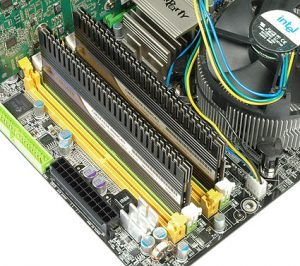 A pair of DDR3 Corsair RAM DIMMS with heatspreaders in their slots on a motherboard