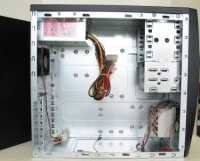 Inside an empty desktop PC case showing the PSU, case fan and drive bays